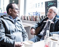 Two men seated in cafe, talking