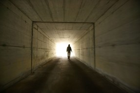 man walking in a dark corridor towards light