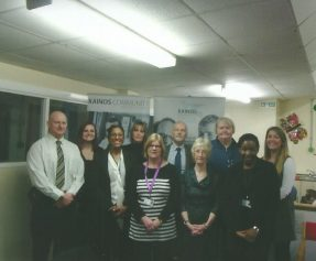 Group of Langley and Kainos staff. They are stood in front of some promotional Kainos banners within an office setting