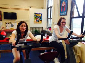 Two members of the Kainos team doing a sponsored cycle for Kainos using exercise bikes
