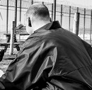 Man in a jacket crouched down in a prison yard
