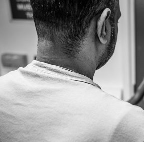 Black and white picture showing the back of a man's head in a white t-shirt in prison