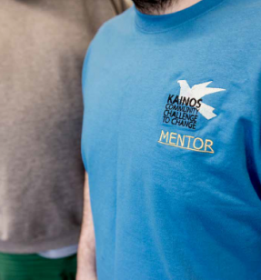 Two men stood next to each other. One is wearing a blue t-shirt with the words 'Kainos Challenge to Change' mentor on it.